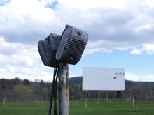 Vintage Drive In Movie Speakers On A Pole With Rundown Screen In Background