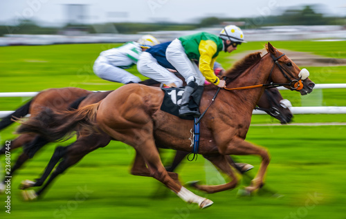 Close-up of jockey and race horse in action, speeding fast motion blur