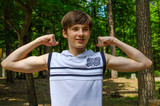 Teenager boy in a white sports shirt without a sleeves shows biceps on his hands