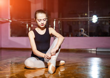 Young Ballerina In Black Body Sitting Down And Tying Pointe Ballet Shoes On Wooden Floor. A Little Ballerina Sitting On A Floor Putting On Her Ballet Shoes.
