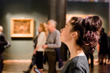 Young Women Waching Arts At The Museum. Excursion With Group