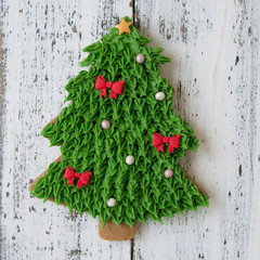 A green glaze Christmas gingerbread cookie in the shape of Chrismas tree on a white wooden table. Close up, selective focus, copy space, flat lay, top view