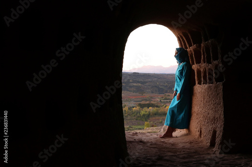 WOMAN WITH A BLUE TUNIC RESTING AT THE ENTRANCE OF A CAVE NEXT TO THE VALLEY Wallpaper Mural