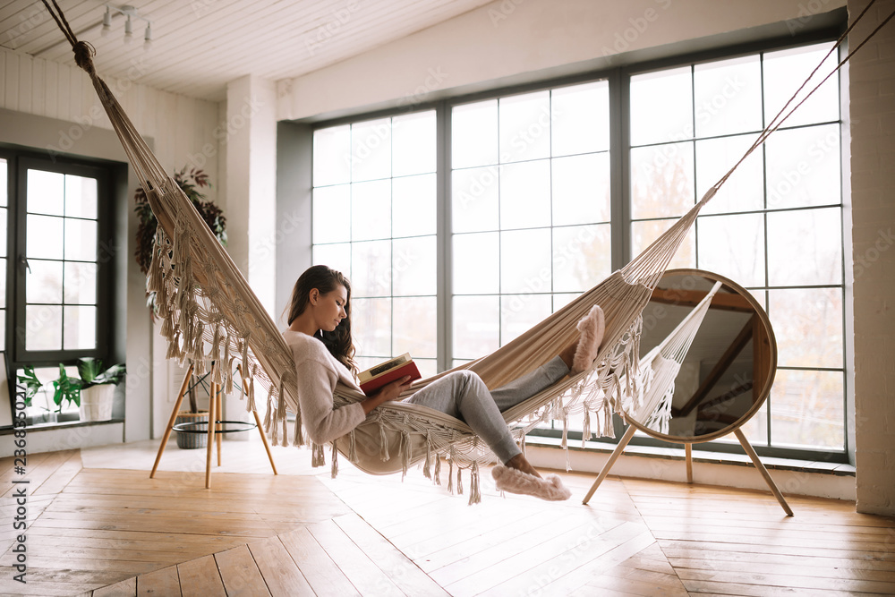 Fototapeta Dark-haired girl dressed in pants, sweater and warm slippers reads a book lying in a hammock in a cozy room with wooden floor and panoramic windows and a round mirror on the floor
