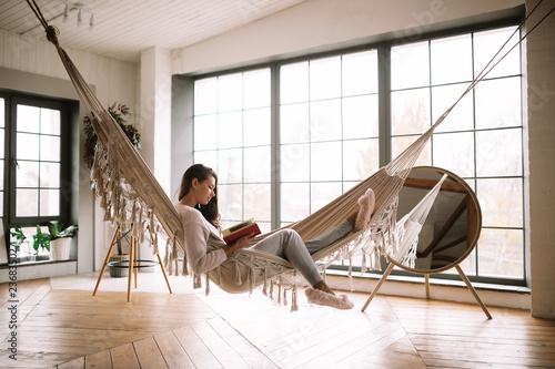 Poster Relaxation Dark-haired girl dressed in pants, sweater and warm slippers reads a book lying in a hammock in a cozy room with wooden floor and panoramic windows and a round mirror on the floor