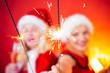 Leinwanddruck Bild - Bengal lights. The festive bright. Christmas Best friends girl. Merry Christmas and Happy Holidays. Joyful friends celebrate christmas on red Background.