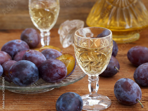 Plum brandy Slivovtz in crystal glasses and plums on wooden background. Traditional Croatian drink.