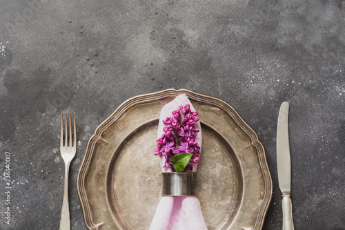 Spring elegant table place setting with violet lilac flowers, silverware on dark table. Top view.