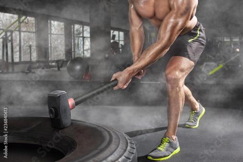 Fotografía  Sport muscular man hitting wheel tire with hammer sledge in the gym