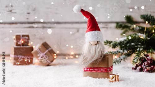 Poster Op straat Frohe Weihnachten - Kleiner Weihnachtswichtel sitzt auf einem Geschenk und freut sich auf Heiligabend