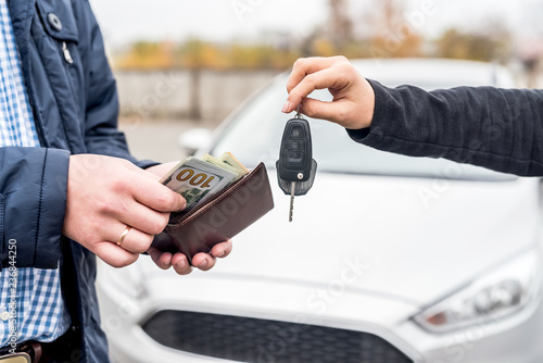 Stickers pour porte Pierre, Sable Hands exchanging with car keys and euro banknotes