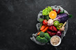 Fresh vegetables and fruits in a wooden box on a black background. Organic food. Top view. Free copy space.