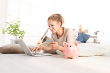 Young Woman Smiling Holding Credit Card And Using Laptop Computer. Piggy Bank On Floor, Online Shopping Saving Concept, Lying On Living Room Wooden Floor In Modern Home, With Copy Space