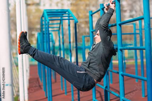 Fotografía  Athlete swings the press on horizontal bar.