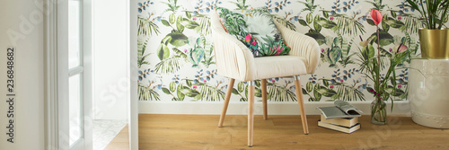 Fototapeta Stylish interior, lovely and bright space to read books or to studdy interior magazines. Floral pattern wallpaper and design armchair. obraz