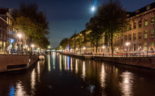 Nighttime On A Canal In Amsterdam With A Full Moon