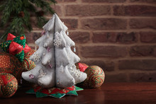 Christmas Tree From Silver Cloth Surrounded By Soft Decorative Toys For Christmas Tree On Brick Wall Background