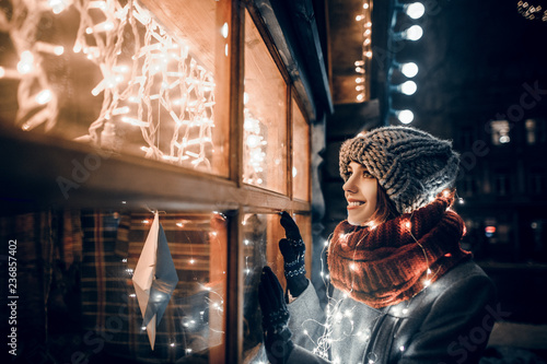 Fotografie, Obraz  Outdoor night photo of young beautiful happy smiling girl looking through shop w
