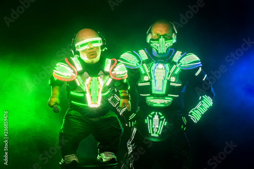 Photo  Mysterious man and midget in black wear, neon mask and gloves