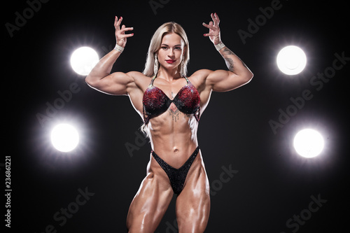 Obraz Bodybuilding competitions on the scene. Women sportsmen and athlete. Black background with lights. - fototapety do salonu