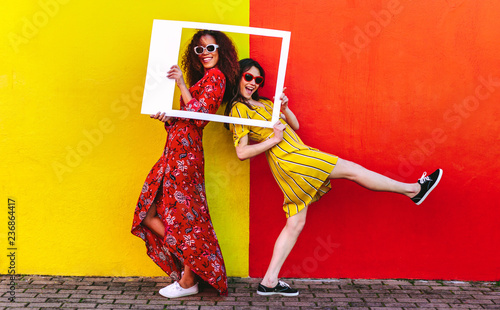 Girls posing with empty picture frame