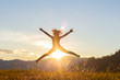 Silhouette of happy child jumping playing on mountain meadow at sunset time
