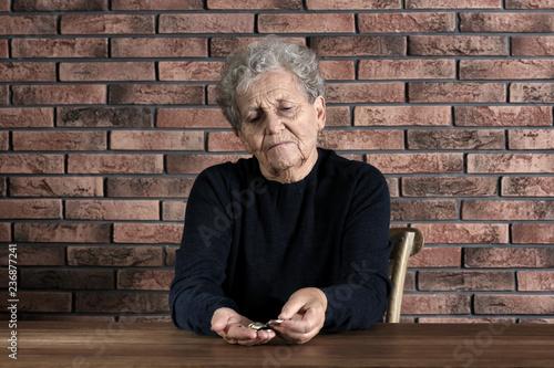 Fényképezés  Poor elderly woman counting coins at table