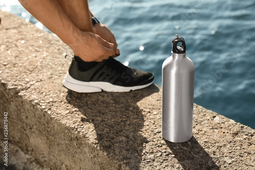 Young man tying shoelaces near bottle of water at riverside on sunny day