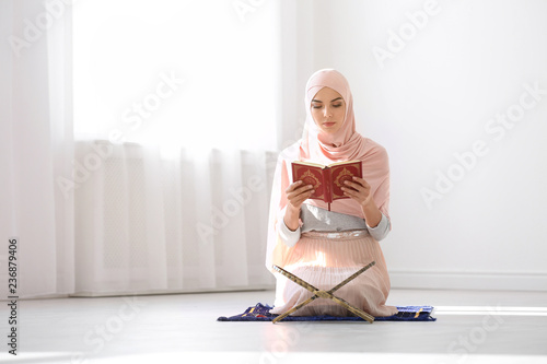 Muslim woman in hijab reading Koran indoors