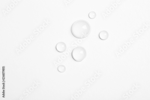 Water drops on white background, top view