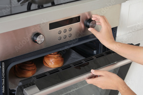 Young woman baking buns in electric oven, closeup