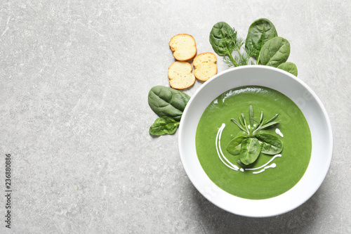 Flat lay composition with fresh vegetable detox soup made of spinach and space for text on table