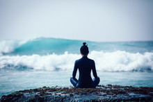 Woman Meditation At The Seaside Cliff Edge Facing The Coming Strong Sea Waves
