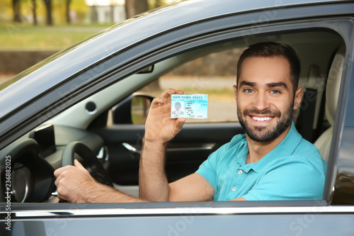 Fotomural Young man holding driving license in car