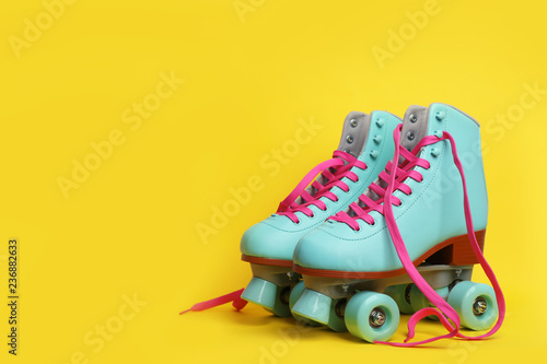 Pair of stylish quad roller skates on color background Canvas Print