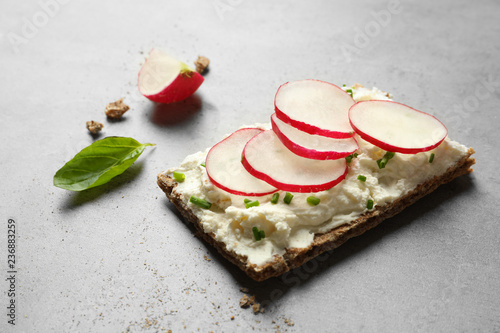 Tasty snack with cream cheese and radish on gray table
