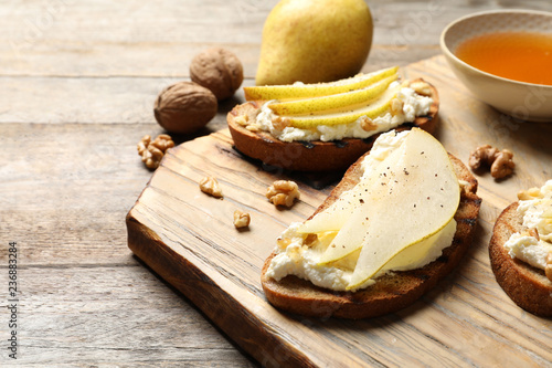 Toasted bread with tasty cream cheese and pear on wooden table. Space for text