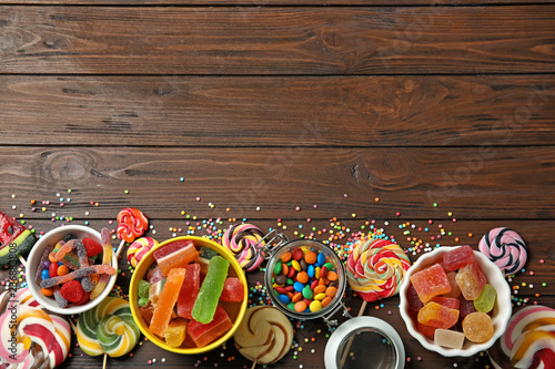 Flat lay composition with different yummy candies and space for text on wooden background