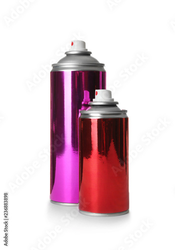 Different cans of spray paints on white background