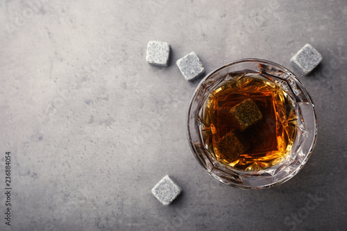 Golden whiskey in glass with cooling stones on table, top view. Space for text