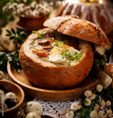 Easter polish sour soup (Żurek) made of rye flour with smoked sausage and eggs served in bread bowl. Traditional polish  Easter dish