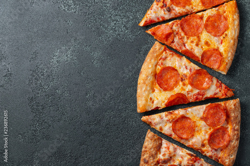 Canvas Prints Pizzeria Cut into slices delicious fresh pizza with sausage pepperoni and cheese on a dark background. Top view with copy space for text. Pizza on the black concrete table. flat lay