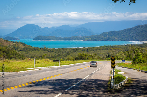 Paraty, Brazil - Feb 20th 2013 - A car driving in a road through a scenic place with a tropical forest in the background in a summer blue sky day in Brazil