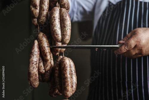 Fotografía Butcher with smoked sausages on a string