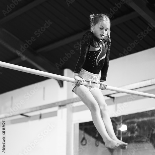In de dag Gymnastiek Young gymnast on a horizontal bar
