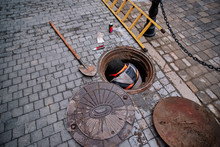 Working Man Comes Out From The Sewerage Hatch In The Ground On City Street. Repair Of Sewage Or Underground Utilities, Nightman Cleans Drains, Cable Laying. Worker On Street Cleaning Pipe.
