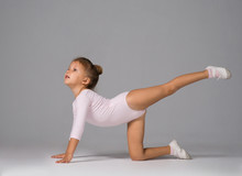 The Little Girl Is Engaged In Gymnastics