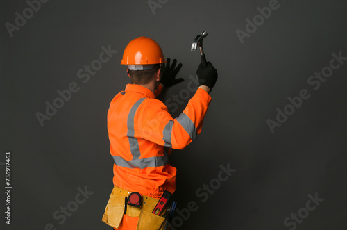 Fotografie, Obraz Builder worker is hammering a nail into the wall by the hammer in his hand