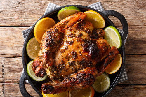 Delicious baked chicken in a spicy citrus marinade close-up in a frying pan. Horizontal top view