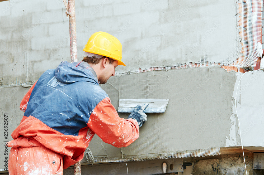 Fototapeta facade work. builder plastering outside wall with putty knife float